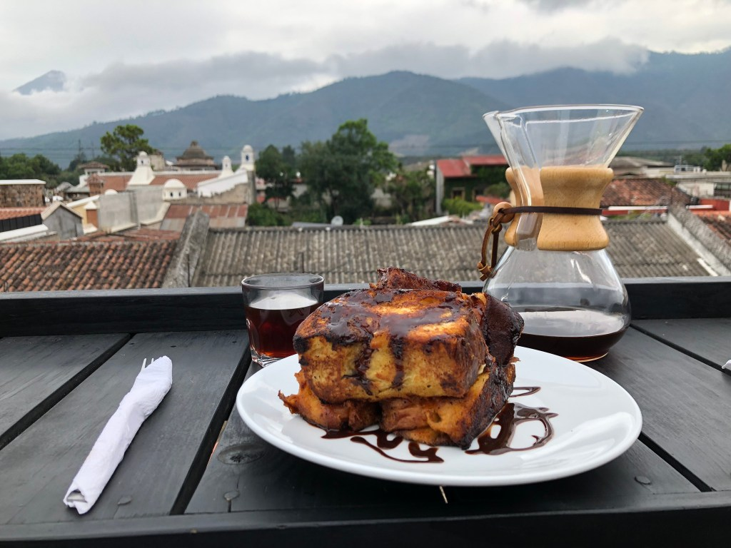 Photo taken on the terrace of Bona Vista of a plateful of French Toast & a Chemex with coffee. Cloud covered mountain range in the background.