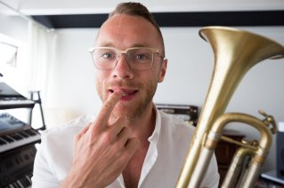 Ari Bragi shows a mark on his lips that he got from years of playing the trumpet.