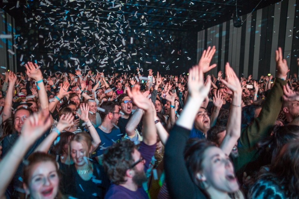 A crowd screams as confetti falls from the ceiling