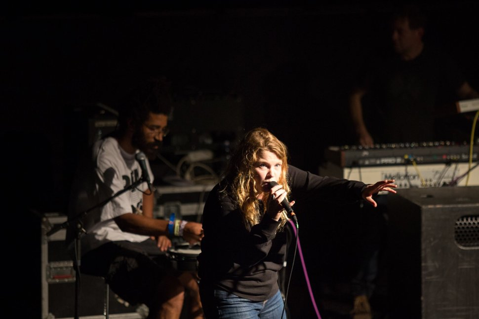 A photograph of Kate Tempest and her drummer performing on stage. She is holding a microphone with her hand outstretched to the crowd.