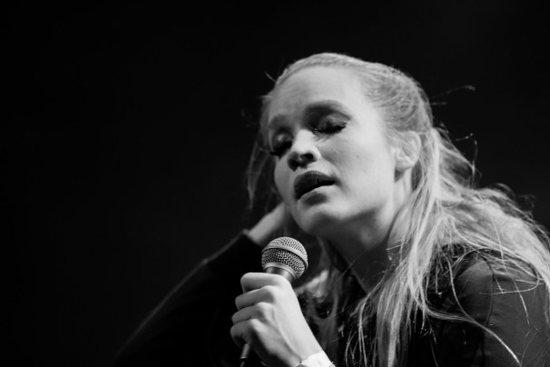 Milkywhale in black and white, singing into a microphone emotionally