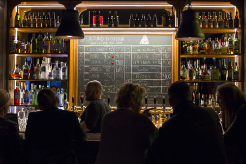 An interior of a bar with a chalk board displaying Icelandic Craft Beer