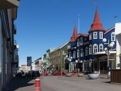 Akureyri's main street, lined with shops and bars by Art Bicnick