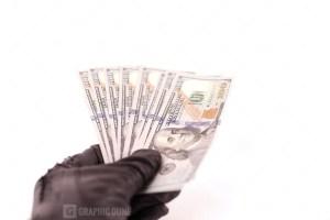 Black glove holding dollars