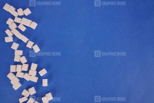 Cubes of white sugar on navy background