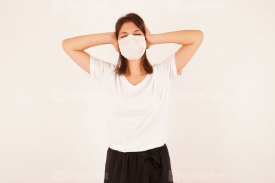 Young irritated woman in medical mask