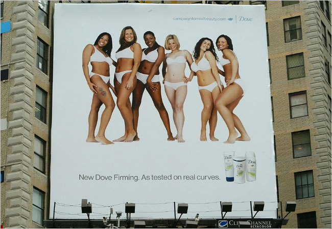 A Dove billboard depicting average, racially diverse women clad in white undergarments, smiling. Text underneath them reads