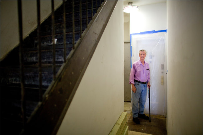 """Mr. Burke says he has spent $13,500 on repairs and $11,000 taking his landlords to court over the conditions. """"It's been hell,"""" he said. """"Now you see, it's no bargain."""" (Photo by Robert Caplin for The New York Times)"""