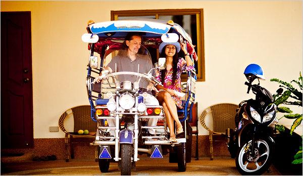 Joseph and Nui Davis in their custom three-wheeled samlor.  Photo:  Justin Mott for The New York Times