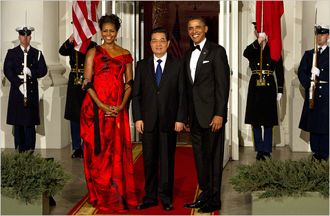 Mrs. Obama wore a red silk organza dress, with a streaky print of black petals, by Sarah Burton of the London house Alexander McQueen.