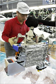 A Nissan employee installs a battery-charger component for a Leaf vehicle at a plant in Yokosuka City, Japan.