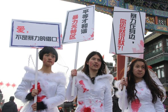 """On Valentine's Day in Beijing, women dressed in white bridal gowns smeared with red paint to protest domestic violence. The women's posters read, left to right: """"Love is no excuse for violence""""; """"Only Equality is Harmonious""""; """"Violence is not a Special Zone""""; """"When Violence is around you, are you still silent?"""""""