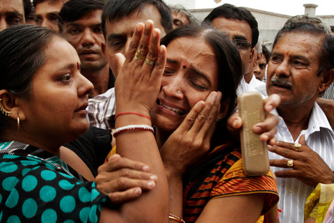 A relative of one of the convicted persons, center, grieves as the convicts are led away after the verdict in Mehsana, Gujarat on July 30, 2012.