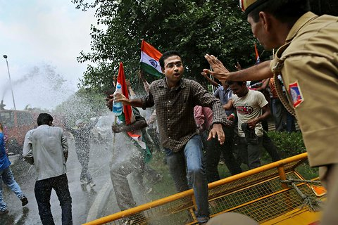 A protester jumped over a police barricade during a demonstration near the prime minister's residence, led by India Against Corruption member Arvind Kejriwal, in New Delhi, Aug. 26, 2012.