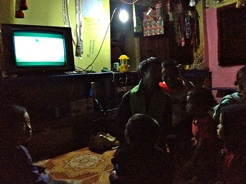 As a generator hums outside, villagers gather in the headman's house to watch Thai soap operas.