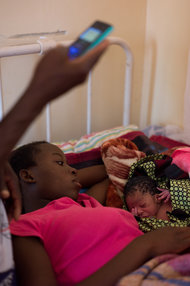 Remind MI agent Mildred Kawala records the birth of Lonar Hamuzala's newborn baby boy at the Nameebo Rural Health Centre in Zambia's Southern Province.