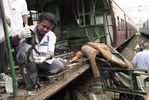 A forensic expert collecting samples from a damaged train coach after a series of bomb blasts in Mumbai, Maharashtra on July 12, 2006.