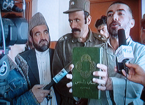 A still from a television program that shows Abdul Rahman, right, who converted from Islam to Christianity, holding a translated version of the Bible at a court in Kabul, Afghanistan, on Mar. 23, 2006.