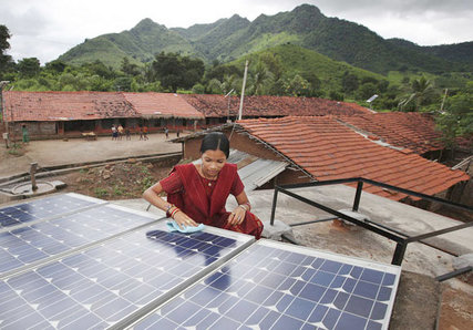 A solar engineer cleans a solar array in a rural village of Puttur in Karnataka state in India. The solar array powers a school that now has extra classes for students at night thanks to the additional power.