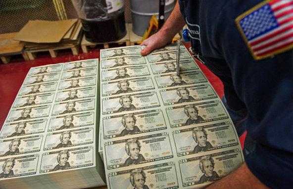 A pressman picks up stacks of $20 bills at the Bureau of Engraving.
