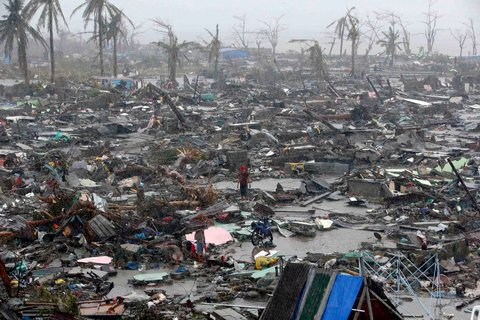 People stood among the ruins of houses in Tacloban after the typhoon tore through the central Philippines.
