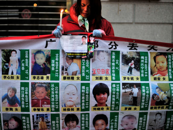 A woman holds a candle behind a board displaying photos of missing children. The Chinese police said they rescued 382 babies in an operation that broke up four major Internet-based baby-trafficking rings.