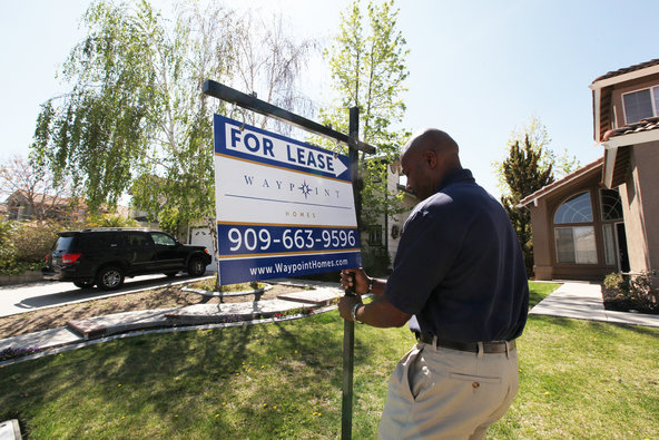 """Hamilton Hanley, an inspector for the Waypoint Real Estate Group, posted a """"for lease"""" sign at a property in San Bernardino."""