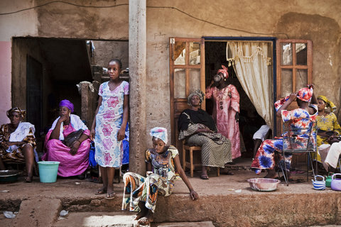 Women sat outside the bride's family home during a rare moment of calm at a wedding celebration in Bamako.
