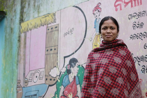 Chandramani Jani in front of a public awareness mural about toilets and sanitation by her home in Chakarliguda.