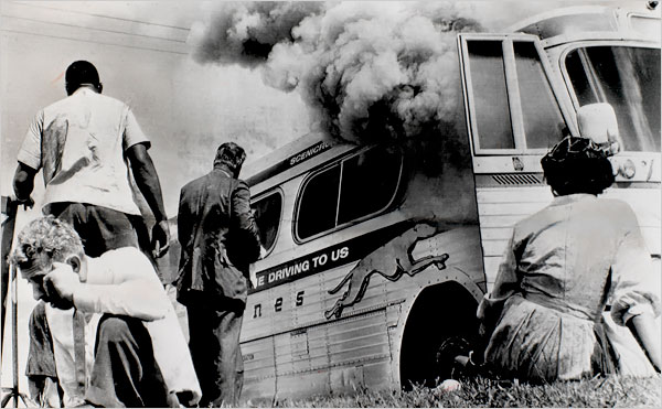 A Freedom Ride bus is fire-bombed outside Anniston, AL, in 1961.