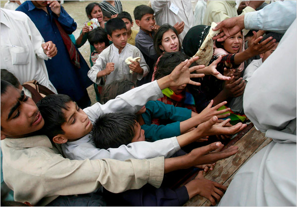 Credit: Reuters, Children displaced from Buner Reach for Food at UN Camp