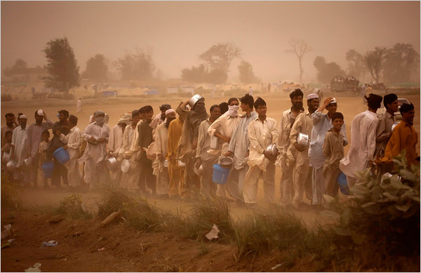Displaced people lined up for the daily food ration during a sand storm at the Chota Lahore refugee camp.