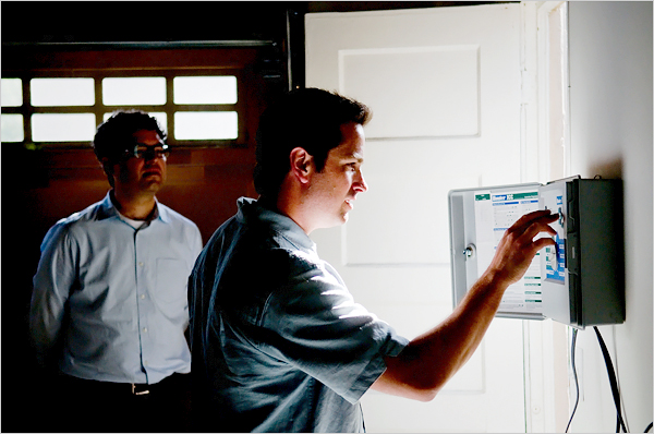 Mr. Pelletier looks at the couples irrigation controller in their garage, which they had considered insulating to use as an office and music studio. He also suggested insulating the attic to save on heating and cooling costs.