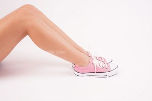 Cropped image of woman legs in stylish sneakers