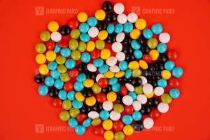 Colorful candies isolated on red background stock photo