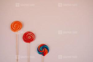 Colorful lollipops on purple background