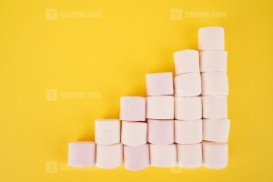 Growing bar chart with marshmallows on yellow background