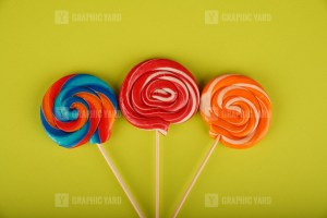 Spiral colored round lollipops on green background