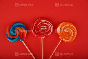 Spiral colored round lollipops on red background