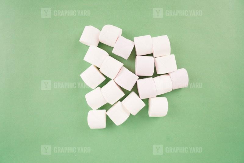 White marshmallow on green stock photo