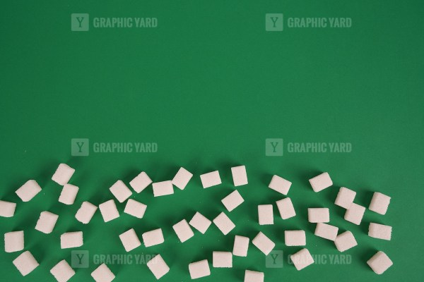 White sugar on green background