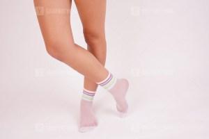 Woman legs in white socks in the studio