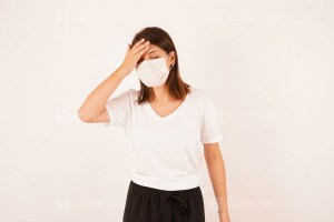 Woman in medical mask touching forehead