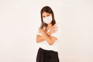 Woman in medical mask with crossed arms