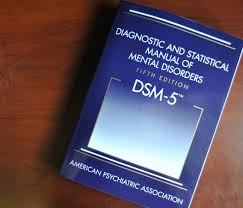 A top down photo of the front cover of the Diagnostic and Statistical Manual of Mental Disorders Fifth Edition. Also known as DSM-5; the font cover is blue, with the title at the top and the authors, the American Psychiatric Association, at the bottom.