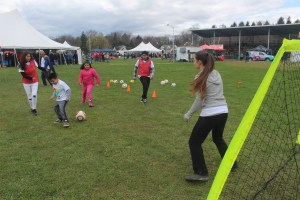 A photo of kids playing soccer while an adult guards the goal.