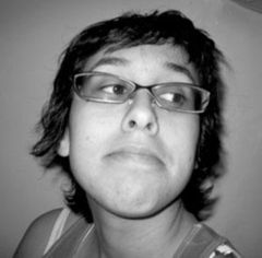 A black and white photo of Nadya Gomez looking away from the camera. She has a slight smile and is wearing glasses.