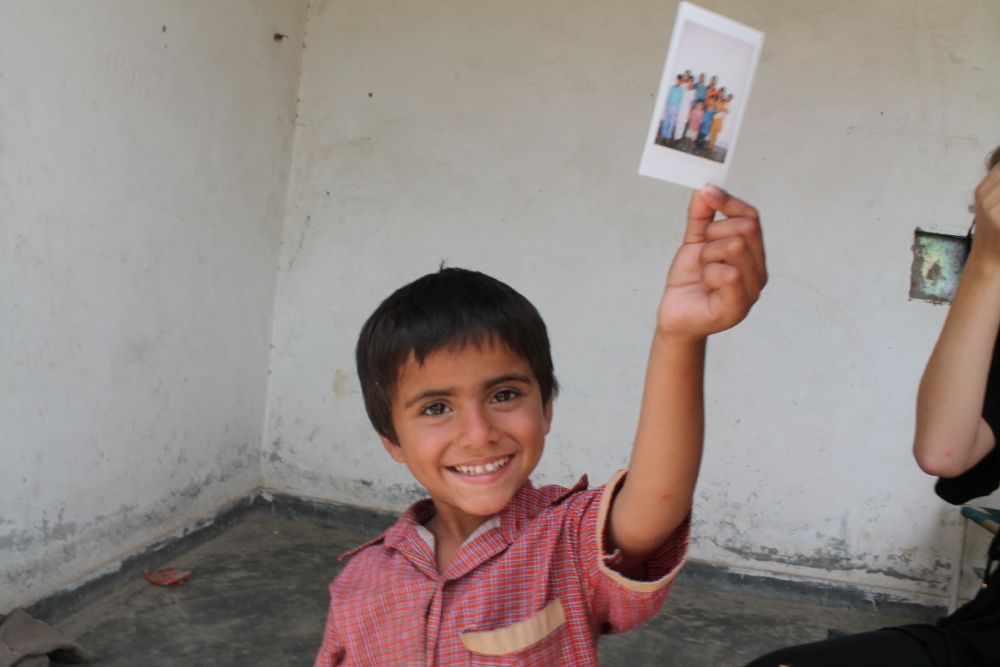 Sameer, one of the family's eight children proudly holds up a memory that will last a lifetime.