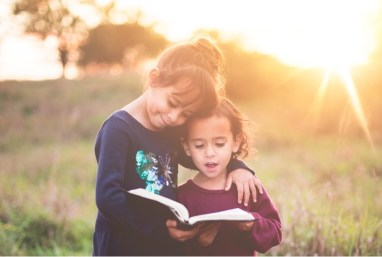 Sisters Looking at a book with sunlight in the background.