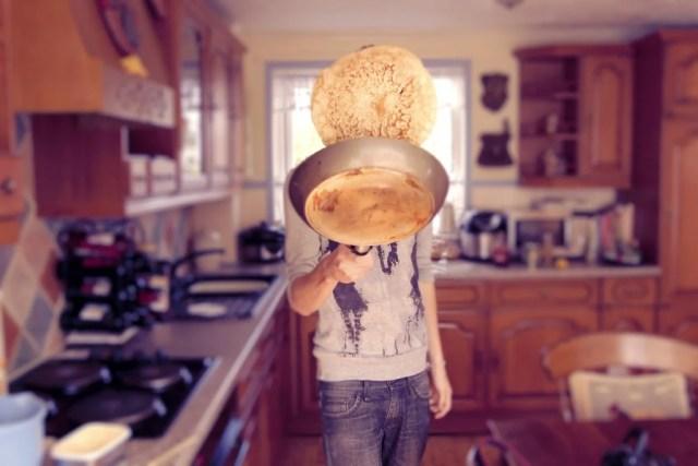 мужчина готовит блины
